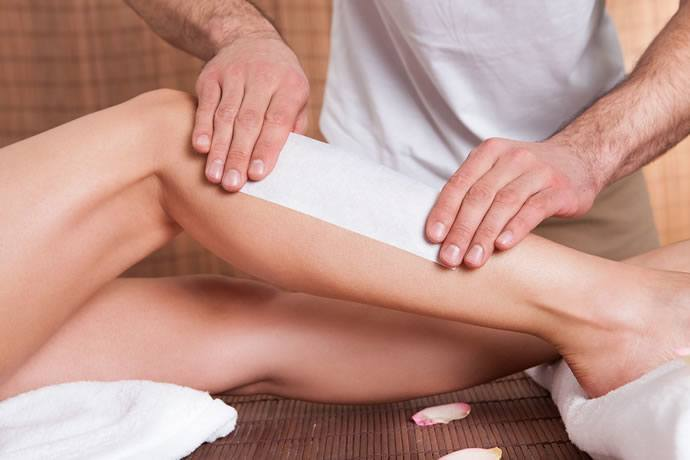 Woman has her leg waxed at a salon