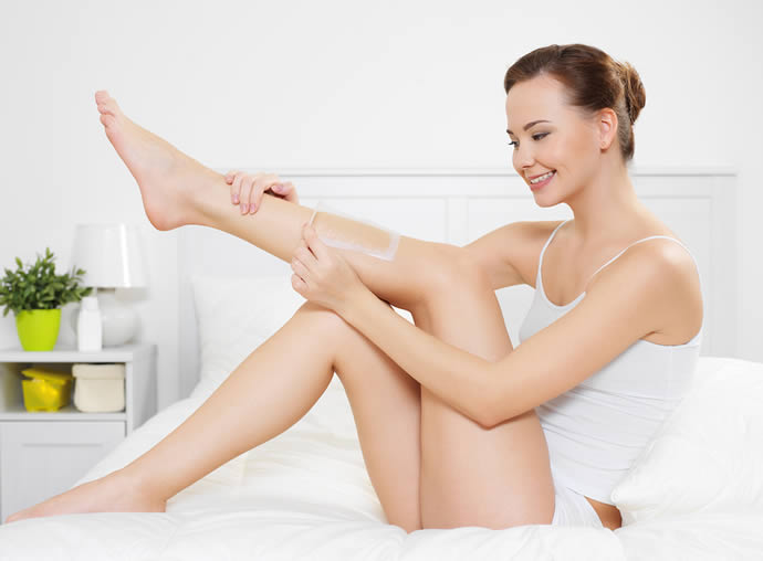 Woman waxing legs with cold wax